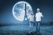 Happy couple walking holding hands against large moon over paris