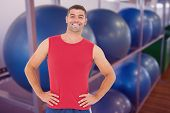 Fit man smiling at camera against exercise balls on rack in studio