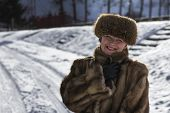 Mature woman in a fur coat with snow