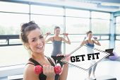 The word get fit and smiling woman lifting weights while women doing aerobics against badge