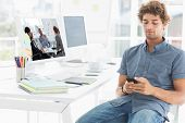 Positive business group having a meeting against man text messaging in a bright office