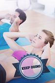 The word keep going and determined young couple doing sit ups at gym against badge