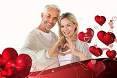 Happy couple forming heart shape with hands against valentines heart design