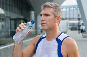 Athletic Man Drinking Water After Running Session In The City
