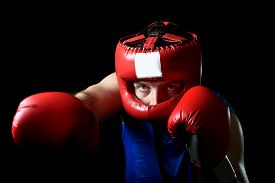 image of headgear  - amateur boxer man training shadow boxing with red fighting gloves and headgear protection throwing vicious right punch attack isolated on black background - JPG