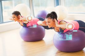 foto of sportswear  - Two fit women exercising on fitness balls in gym against fitness interface - JPG