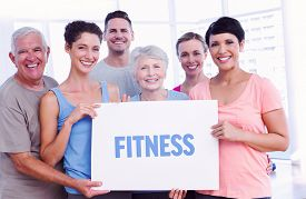 pic of senior class  - The word fitness against fit people holding blank board in yoga class - JPG