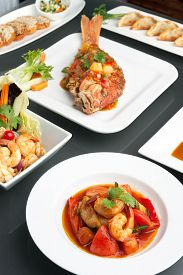 stock photo of red snapper  - Variety of Thai style whole fish red snapper sweet and sour shrimp gyoza dumplings sesame breads seafood salad and other spicy Thai dishes - JPG