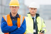 stock photo of coworkers  - Portrait of confident worker standing with coworker in shipping yard - JPG