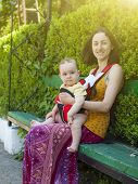 image of sling bag  - Young mother walking in the Park and holding a small child in a Baby Carrier bag - JPG