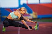 stock photo of race track  - young runner sporty woman relaxing and stretching on athletic race track - JPG
