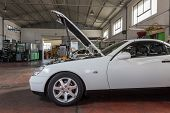 stock photo of muscle-car  - car with the hood open in repair workshop - JPG
