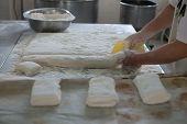 image of home-made bread  - A baker cutting freshly made bread dough on a tray showing raw Ciabatta bread ready to be baked - JPG
