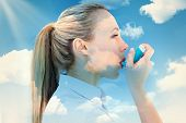 picture of inhalant  - Pretty blonde using an asthma inhaler against blue sky - JPG