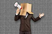 picture of anonymous  - Anonymous businessman holding a megaphone against grey background - JPG