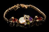 stock photo of precious stone  - Beautiful golden bracelet with precious stones on black background - JPG