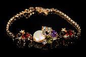 pic of precious stones  - Beautiful golden bracelet with precious stones on black background - JPG