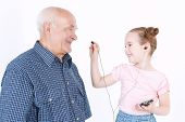 stock photo of granddaughters  - Portrait of a small pretty granddaughter using a smartphone and proposing a headphone to her grandfather wearing blue checkered shirt while he is smiling - JPG