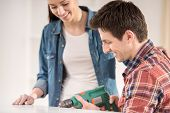 stock photo of hand drill  - Young man building furniture using hand drill at home - JPG