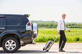 foto of leaving  - Full length side view of young businessman with suitcase leaving broken car at countryside - JPG