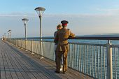 stock photo of track home  - A girl in a track suit and a guy in his army suit turning away from the camera looking at the sea while standing at the pier at sunset hour on a summer day with no clouds in the sky - JPG