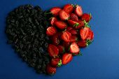 stock photo of prunes  - Strawberry and prunes in shape of heart on blue background - JPG
