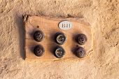 stock photo of electric socket  - Two old electrical sockets and four switches on wooden plate on a rough wall - JPG
