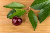 image of bamboo leaves  - Ripe berries of sweet cherry with leafs on wooden bamboo board - JPG