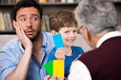 stock photo of psychologist  - Little boy and his father talking with psychologist - JPG