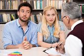 image of psychologist  - Young nervous couple talking with psychologist - JPG