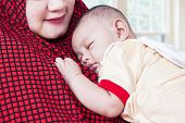 stock photo of innocence  - Closeup of innocent baby boy sleeping in the bedroom on the mother - JPG