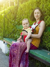 stock photo of sling bag  - Young mother walking in the Park and holding a small child in a Baby Carrier bag. ** Note: Soft Focus at 100%, best at smaller sizes - JPG