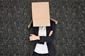 stock photo of lifting-off  - Businesswoman lifting box off head against black background - JPG