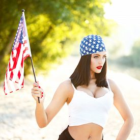 stock photo of independent woman  - Sexy brunette woman with usa headscarf and flag outdoor portrait - JPG