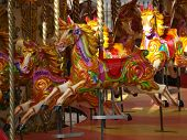stock photo of suny  - vivid carousel with colourfull wooden horses shining on the sun - JPG