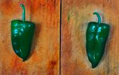stock photo of poblano  - Poblano chili peppers over wooden board background - JPG