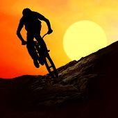 Silueta de un hombre en bicicleta de muontain, puesta del sol