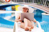 Young women relaxing near waterpool with laptop.