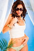 Glamour style photo of beautiful girl in sunglasses posing in summerhouse on beach. Retouched