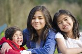picture of scandinavian descent  - Two sisters and their disabled little brother sitting together at the park biracial part Thai - JPG