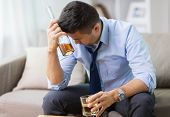 alcoholism, alcohol addiction and people concept - male alcoholic with bottle and glass drinking whi poster