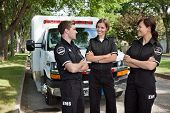 Group of 3 EMS workers standing in front of ambulance visiting