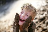 A Cute Little Boy Child Is Laughing As He Plays Outside In The Mud And Rubs Dirt On His Face With Hi poster