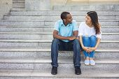 Smiling Mixed Race Man And Woman Sitting At Talking On Staircase. Young African American Man And Asi poster
