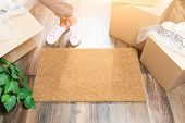 Woman in Pink Shoes and Sweats Standing Near Home Sweet Home Welcome Mat, Boxes and Plant. poster