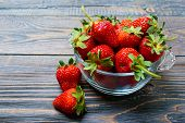 Fresh Ripe Strawberries In A Bowl On A Wooden Table. Freshly Harvested Crop. poster