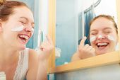 Happy Young Woman Applying Cleansing Moisturizing Skin Cream On Face. Girl Taking Care Of Dry Comple poster