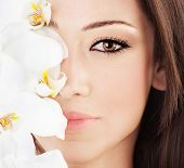 image of female model  - Closeup on beautiful face with white orchid flower perfect clean skin young female portrait beauty and spa concept - JPG