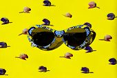Travel, Vacation, Summer Concept. Blue Plastic Sunglasses Over Yellow. Top View Of Sunglasses And Fl poster