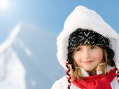 Winter holiday - portrait of cute girl, snowy mountains in background